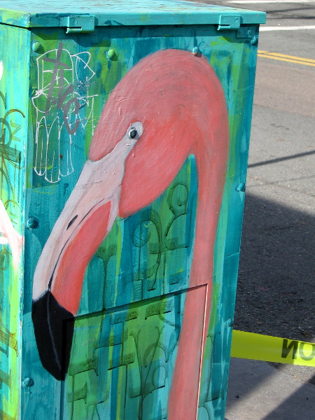 The face of a pink flamingo painted on a utility box!