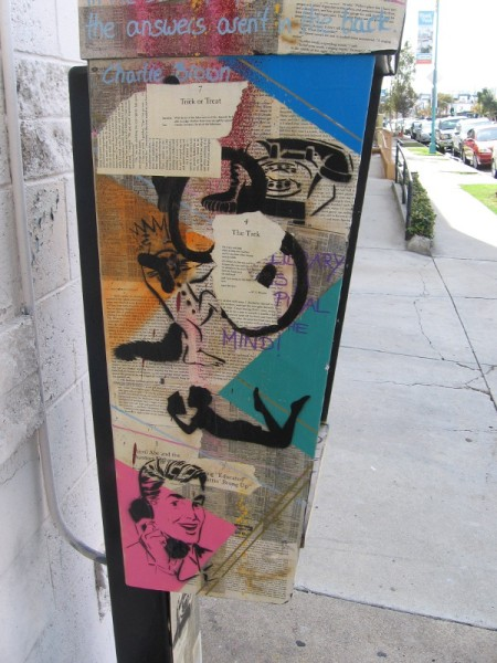 Artistic collage on a public telephone includes the printed word, and various stencil faces and figures.