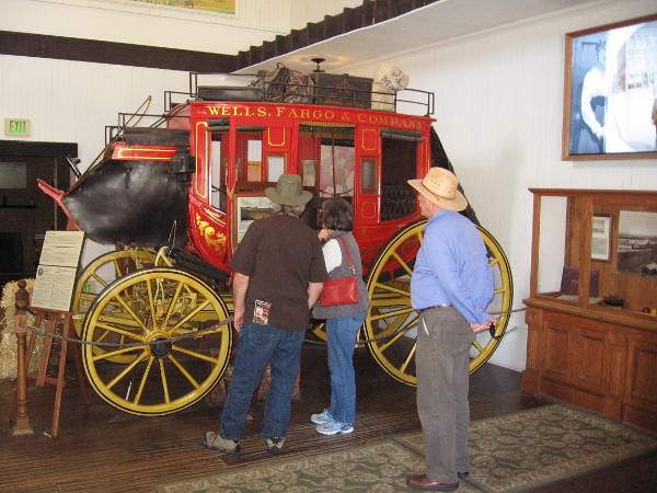 Tourists in Old Town check out a red Wells Fargo stagecoach, which transported mail, gold, goods and passengers in the Old West.