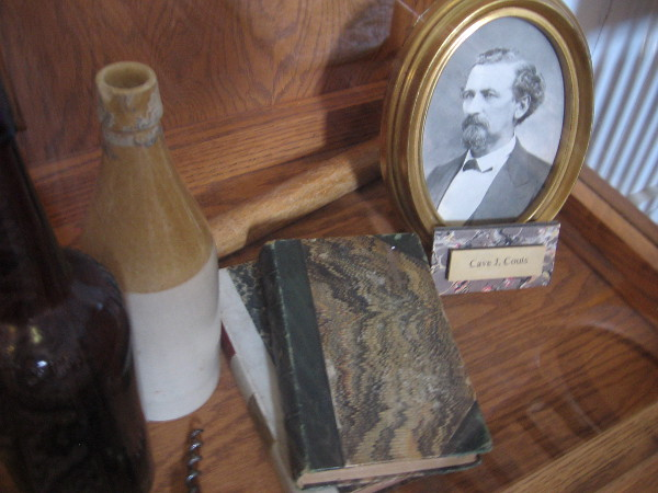 Historical artifacts in a glass display case include books, bottles and a photo of Cave J. Couts.