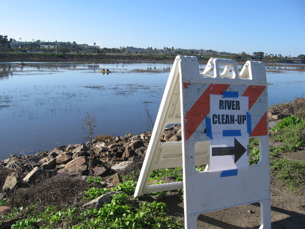 A sign directs people to the river cleanup.