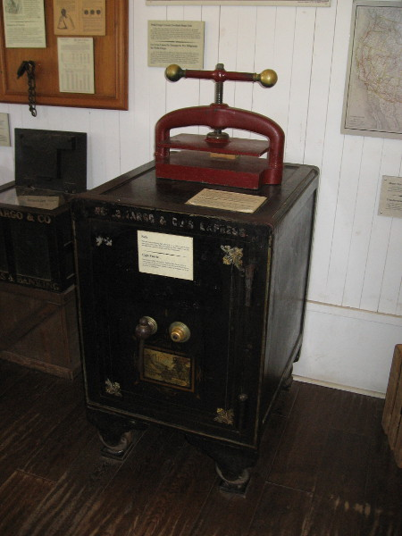 A large old letterpress sits atop a cast iron safe. The safe, made by Herring, Hall, Marvin and Co. in 1885, is filled with concrete and weighs over a ton.