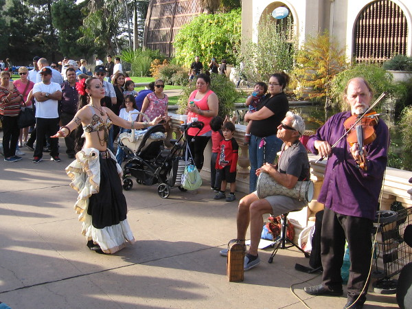 A belly dancer and musicians draw a large crowd near the Botanical Building. The audience is spellbound.