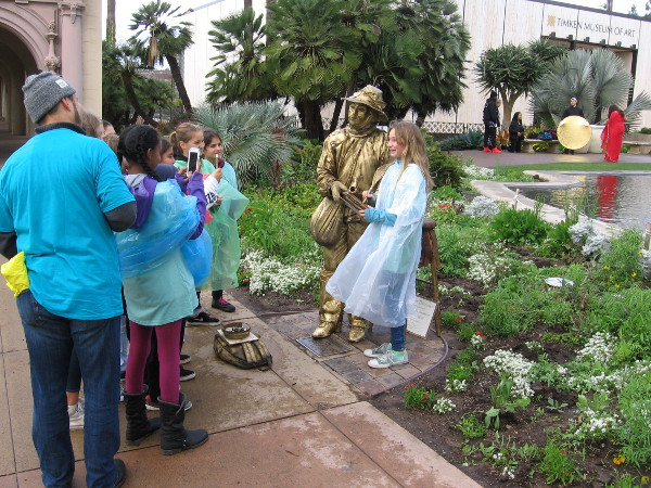 Girls in ponchos take photos with Will the bronze-gold Bard near the Balboa Park reflecting pool after the rain.