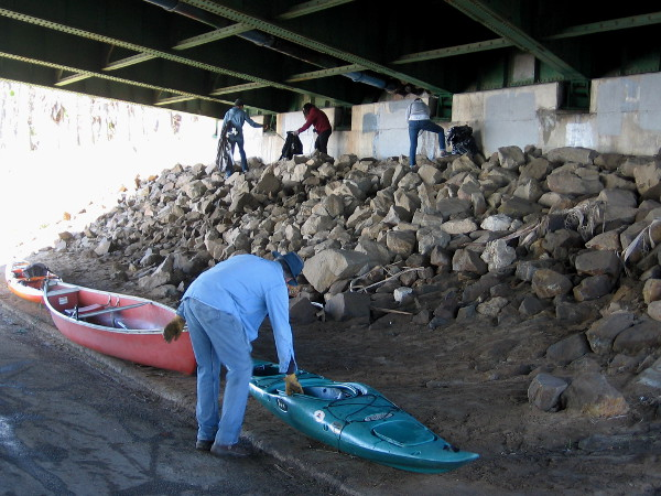 Picking up garbage and readying kayaks underneath the West Mission Bay Bridge.
