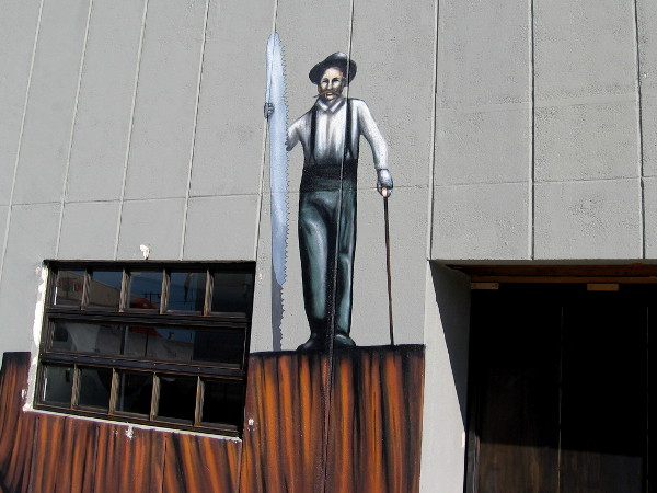 A fourth lumberjack holds a long saw on the side of Made Lumber Supply.