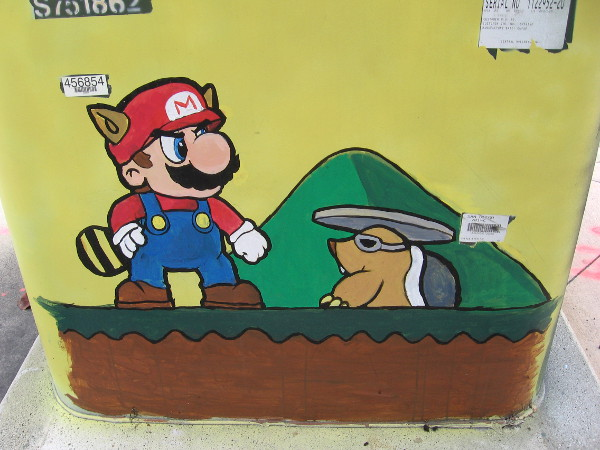 A villainous Rocky Wrench pops out of a hole to attack Mario in this video game street art!