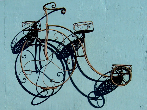 A cool decorative bicycle suspended from a wall. I spotted this at the Reusable Finds resale and repurpose store , near their entrance.
