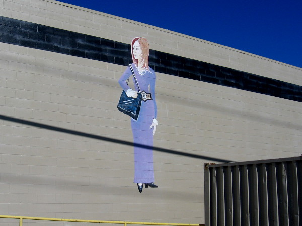 Mural of a fashionable lady on the wall behind the Leatherock leather goods store.