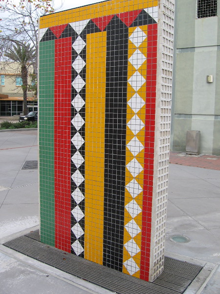 The beautiful patterns on this wall-like artwork are composed of many brightly colored tiles.