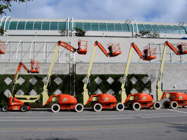 Engine powered articulating boom lifts in a row behind the San Diego Convention Center.
