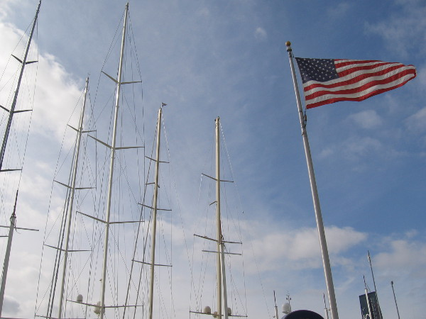 The high masts of super yachts rise behind the convention center into the sky.