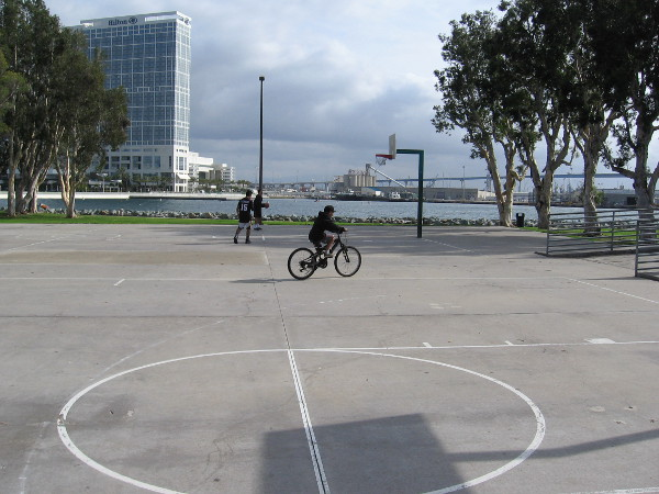 Two basketball players and a bicyclist. It's a fairly quiet day at Embarcadero Marina Park South.