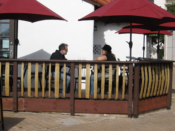 A couple enjoys outdoor conversation at Seaport Village's San Pasqual Wine Tasting Room.