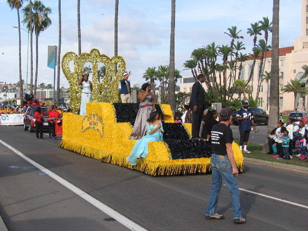 Here comes a bright yellow float carrying some beauty queens!