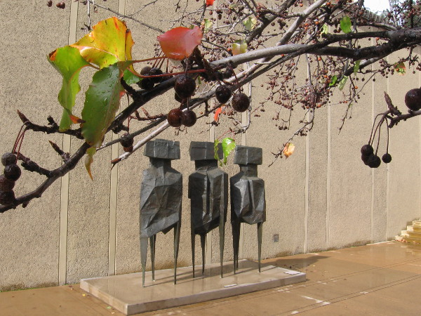 Dripping branches and leaves seem to overhang The Watchers. This outdoor sculpture is by artist Lynn Chadwick.