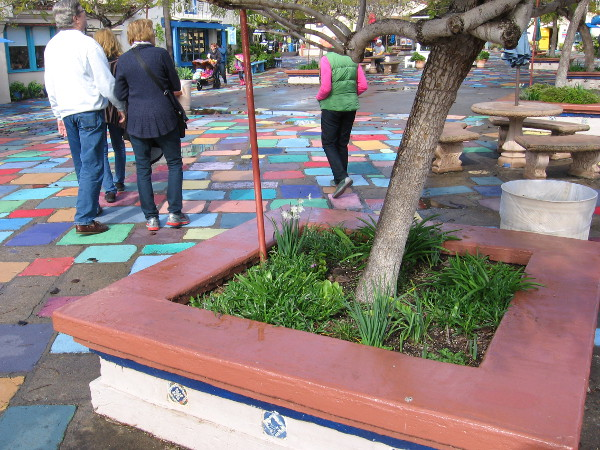 The colors of the tiles in Spanish Village's patio are made bold and cheerful with the lingering moisture.