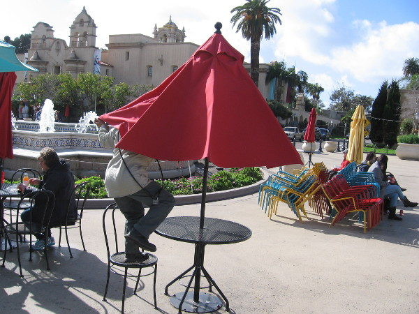 The sun is out after the storm. A Balboa Park ranger opens the colorful table umbrellas in the Plaza de Panama.