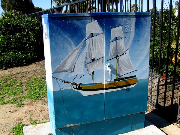 Some street art on a nearby utility box depicts a tall ship on the ocean.