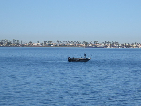 A fisherman out on San Diego Bay. The Coronado Cays are visible across the calm blue water.