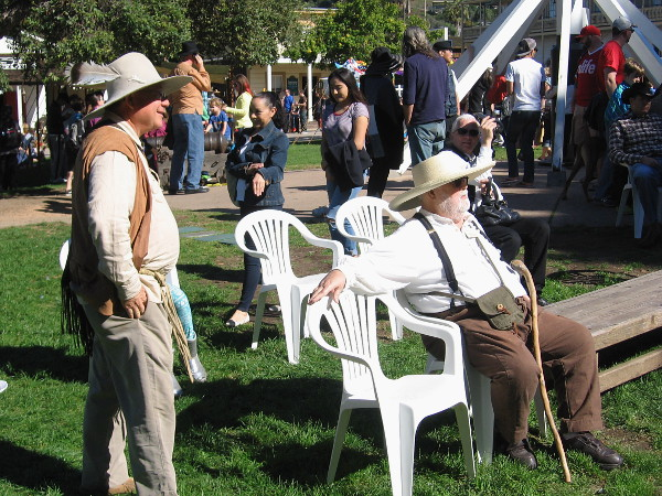 Guys in pioneer clothing just kick back in plastic chairs and watch some dancing and musical entertainment during the event.