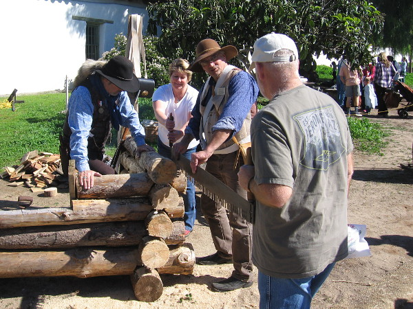 Visitors to Mormon Battalion Commemoration Day try their hand at sawing a thick log!