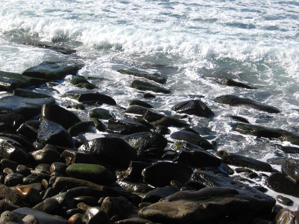 Crashing water meets smooth stones on the ocean shore in La Jolla.