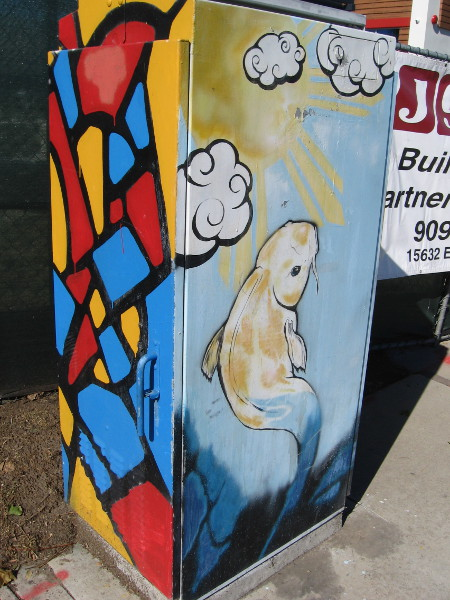 Colors like stained glass and a rising koi on this utility box.