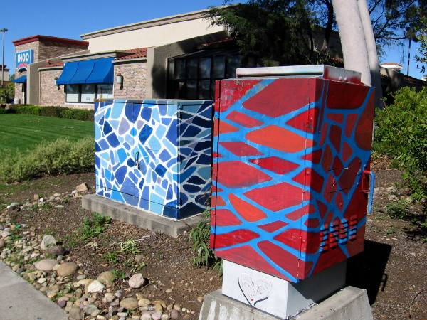 Two colorful electrical boxes along Mira Mesa Boulevard.