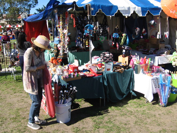Many booths in the park had all sorts of gleaming goods for sale.