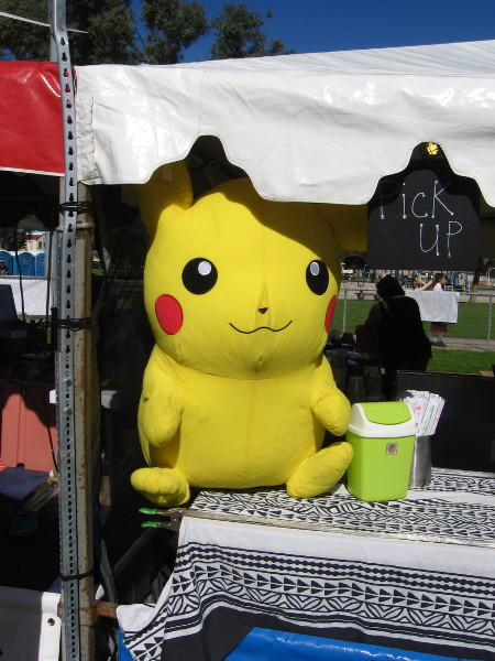 Pikachu sits protecting a spot where food is picked up.