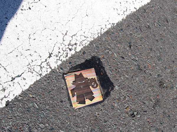 Crossing an intersection in the Gaslamp, I spotted an odd thing at ground level. This tile showing a burglar has been cemented to the asphalt in the middle of the street!