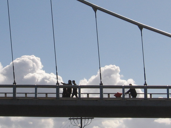 People crossing the Harbor Drive pedestrian bridge seem to walk in the clouds