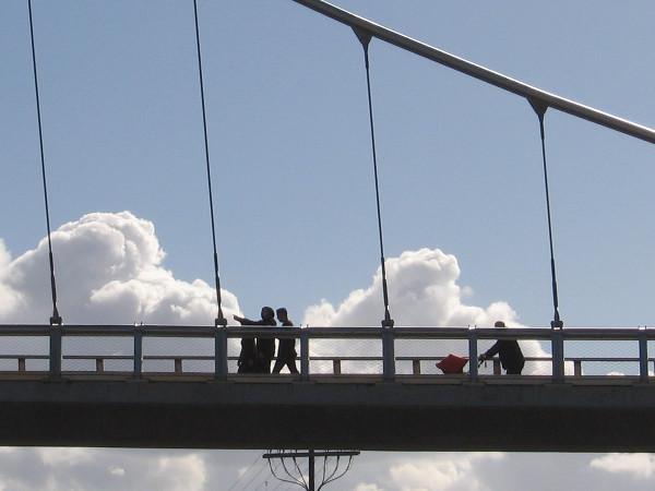 People crossing the Harbor Drive pedestrian bridge seem to walk in the clouds