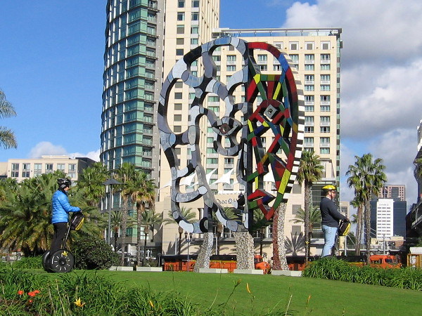 Tourists on Segways pass the Coming Together sculpture by artist Niki de Saint Phalle.