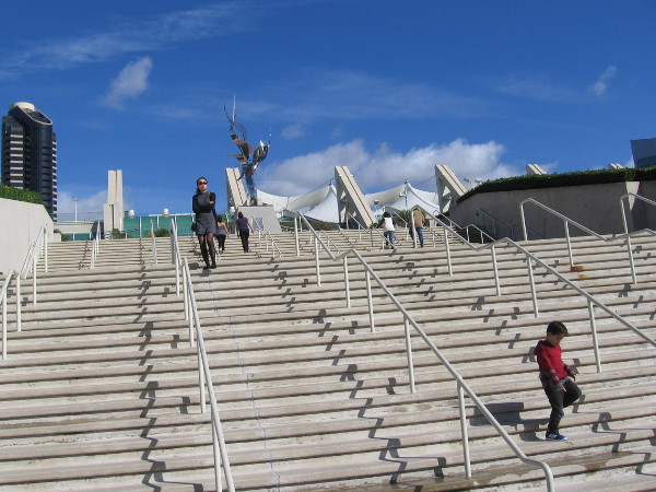 People descend the San Diego Convention Center steps that lead to the Flame of Friendship sculpture.