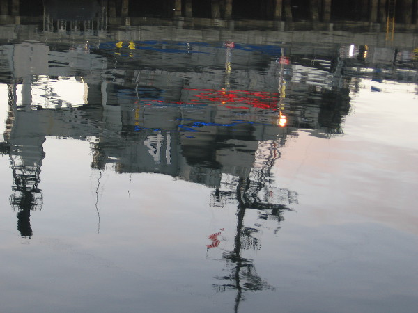 Colorful reflection on San Diego Bay of the USS Midway Museum, seen from the Broadway Pier.