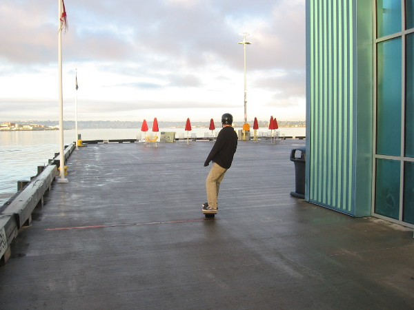 Someone rides out to the end of the Broadway Pier early one Friday morning. Few people are about.