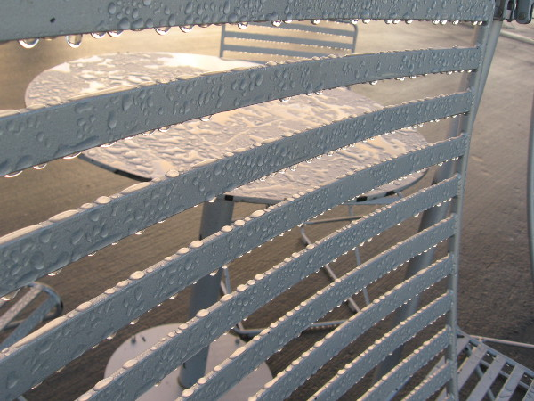 Water droplets cling to the metal seats and tables at the end of the Broadway Pier.