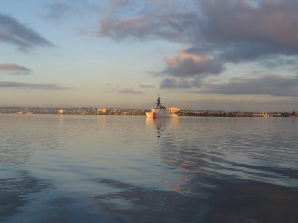 Beautiful clouds and morning light frame a United States Coast Guard Cutter in the middle of San Diego Bay.