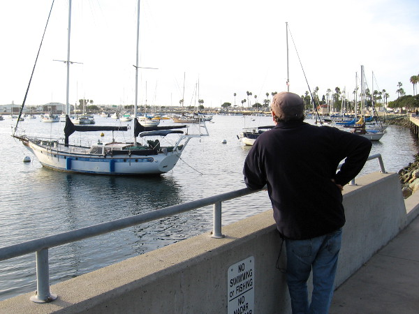 Someone stands by the water one late afternoon gazing at moored boats in the Crescent area of San Diego Bay.