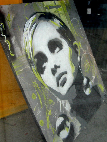 Painting of female face in window of a small shop in East Village containing odd bits of art and miscellaneous used items.