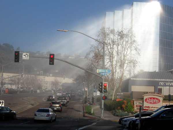 Early morning sunlight reflects from a building's windows in Mission Valley, casting heavenly beams of light through lifting fog.