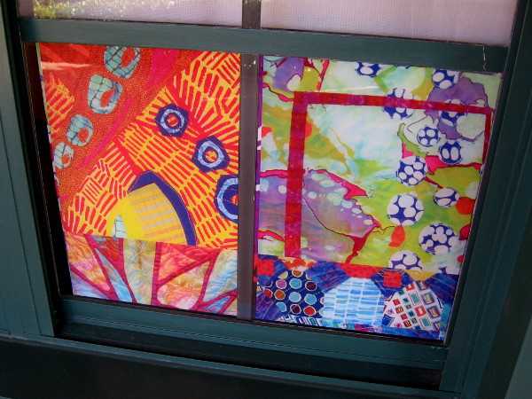 Colorful quilting artwork in a window of the Visions Art Museum at Liberty Station.