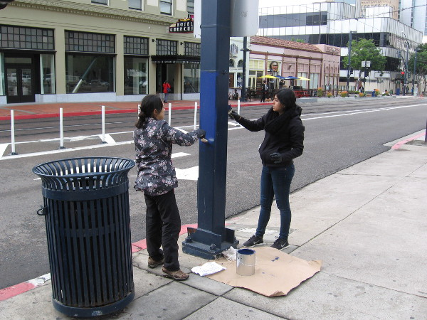 Volunteers in downtown San Diego add a coat of paint to a metal post. A wonderful community project put together by the Downtown San Diego Partnership.