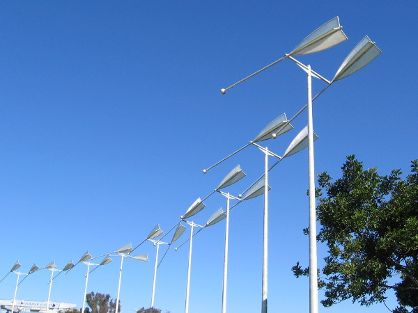Oars in the blue sky change position in the shifting wind. A kinetic artwork landmark in San Diego's South Bay.