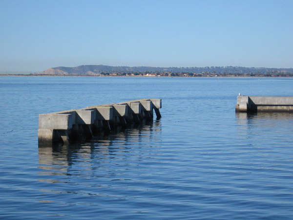 A breakwater by Marine Group Boat Works looks like art on the water. In the distance we can see Point Loma.