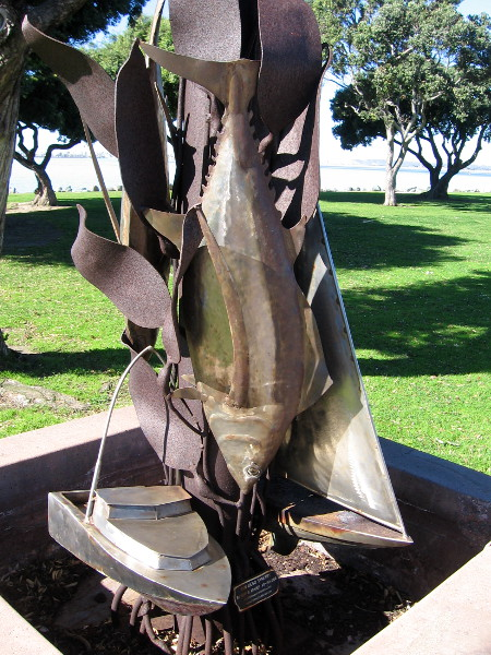 A silvery tuna between a fishing boat and sailboat, at the base of the San Diego Synergy sculpture in Chula Vista.