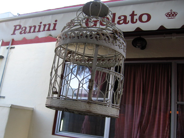 A fancy bird cage dangles beside Pappalecco, a cool Little Italy cafe.