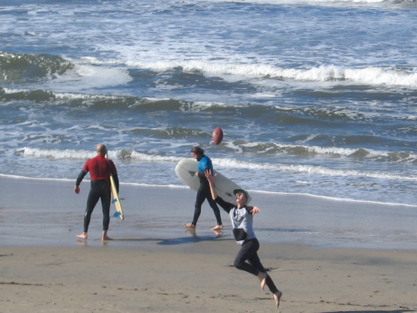 Catching a football on the beach while two surfers head toward the water.